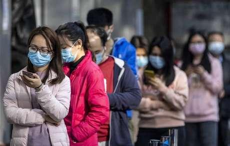 Pessoas fazem fila em farmácia de Guangzhou, na China, para comprar máscaras de proteção