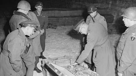 Militares americanos do comando aliado examinam mala de talheres de prata, parte do saque alemão armazenado em uma mina de sal em Merkers