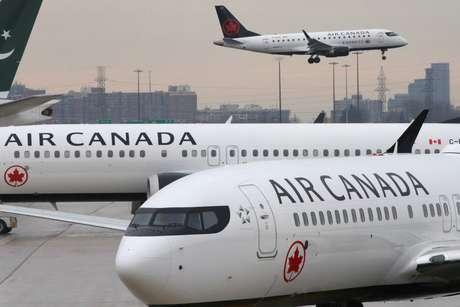 Duas aeronaves Boeing 737 MAX 8 [aradas em aeroporto, enquanto um jato da Embrer voa ao fundo. 13/3/2019.  REUTERS/Chris Helgren