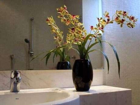2 -Orquídea em vaso preto decora o ambiente do banheiro, por isso observe como cuidar de orquídea.