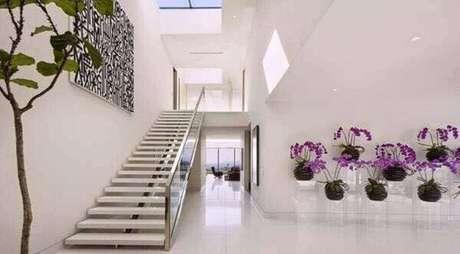 29- Hall de entrada com orquídeas lilás, aprenda como cuidar de orquídea para deixar sua casa linda.