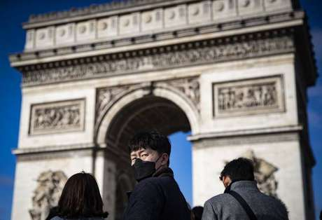 Turistas com máscaras de proteção em frente ao Arco do Triunfo, em Paris