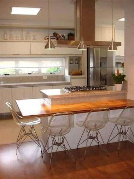 12. Cozinha com cooktop em ilha planejada com bancada de madeira e cadeiras de acrílico transparente – Foto: Webcomunica