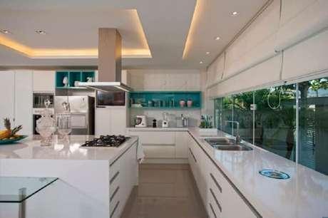 23. Decoração toda branca com nichos azuis para cozinha com fogão cooktop com ilha grande – Foto: Lana Rocha
