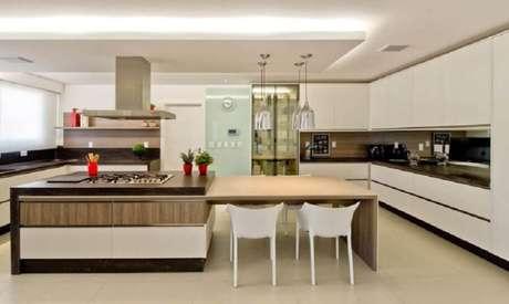 26. Decoração moderna para cozinha planejada com cooktop e bancada de madeira ligada à ilha – Foto: Espaço do Traço