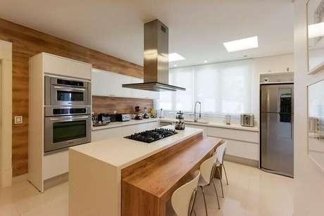28. Decoração em tons claros para cozinha planejada com cooktop e ilha com bancada de madeira – Foto: Jannini Sagarra Arquitetura