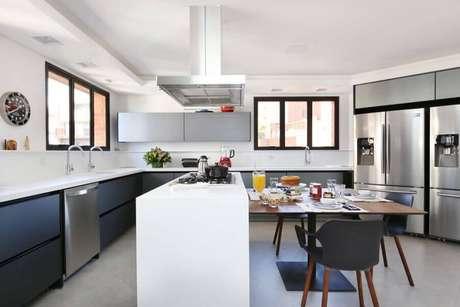 29. Cozinha planejada com cooktop e mesa de madeira – Foto: Start Arquitetura