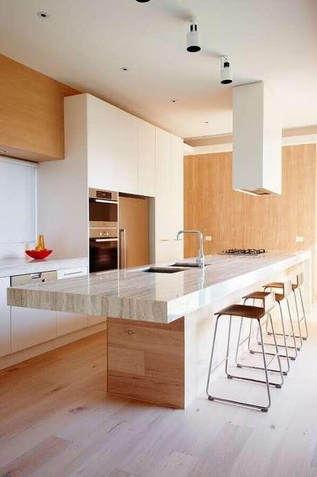 35. Decoração em tons neutros com estilo moderno e sofisticado com pia de cozinha com cooktop instalados em ilha grande – Foto: Arquidicas
