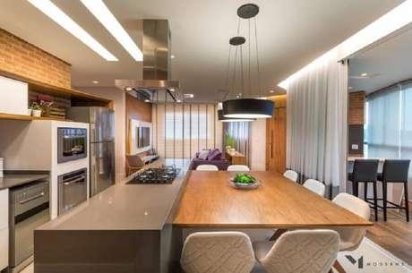 42. Decoração para cozinha planejada com cooktop bem ampla com mesa de madeira integrada à ilha – Foto: Moderne Arquitetura