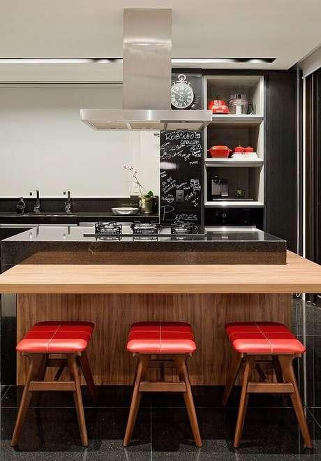44. Ilha de cozinha com cooktop e bancada de madeira com banquetas baixas – Foto: Casa de Valentina