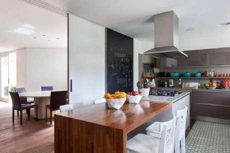 45. Ilha de cozinha com cooktop e mesa de madeira integrada – Foto: Ornare