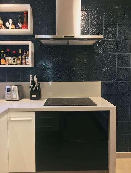 51. Armário de cozinha com cooktop e revestimento azul marinho para paredes – Foto: Pinterest