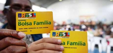 Beneficiários exibem cartões do Bolsa Família; programa contempla famílias com renda mensal de até R$ 178