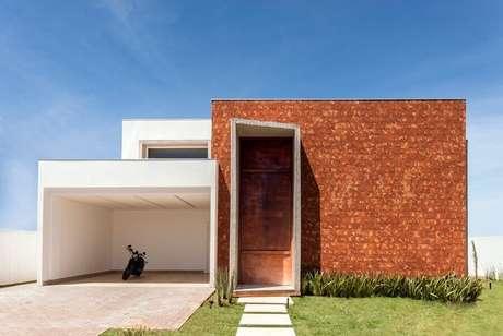 12. Fachada de casa moderna com porta de ferro grande e arrojada – Foto: Casa de Valentina