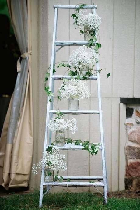 49. Posicione potes de vidro na estante escada e forme lindos arranjos florais. Fonte: Casa e Festa