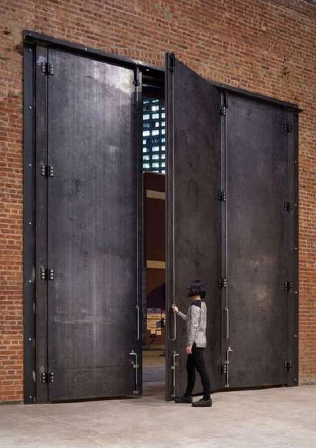 13. Entrada de galpão com porta de ferro grande – Foto: Archinect