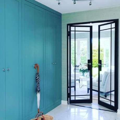 18. Porta de ferro com vidro para hall de entrada com parede azul – Foto: Metal Form