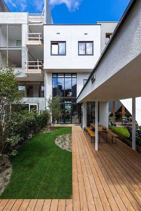 28. Jardim residencial moderno com parte de deck de madeira – Foto: De Architect