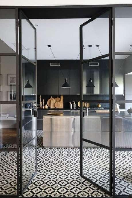 5. Modelo de porta de ferro para cozinha moderna com armários pretos e ilha de inox – Foto: Pinterest