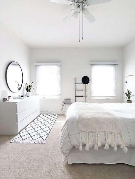 19. Decoração minimalista para quarto branco com espelho redondo e passadeira em frente a cômoda – Foto: Pinterest