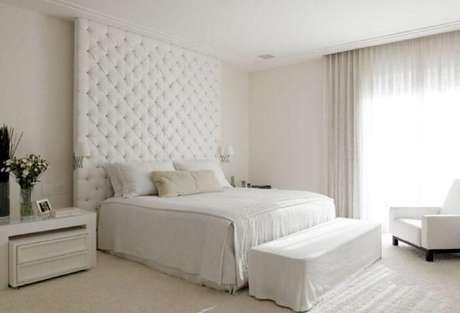 23. Decoração neutra para quarto branco com cabeceira estofada até o teto – Foto: Roberto Migotto