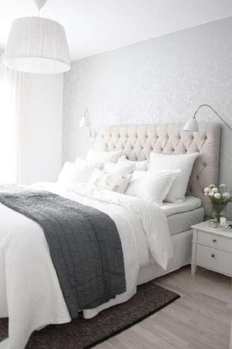 55. Quarto branco decorado com cabeceira capitonê e papel de parede cinza claro – Foto: Sodimac