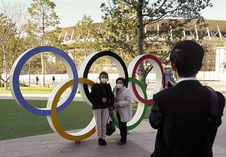 Turistas posam em frente aos anéis olímpicos em Tóquio, Japão