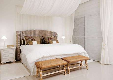 26. Os tecidos dão uma aura esvoaçante para o quarto da casa de praia. Os bancos de vime são responsáveis pela parte rústica. Projeto por Priscila Koch.