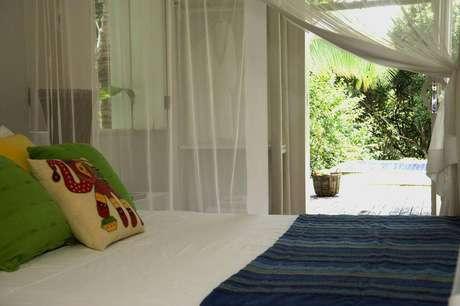 18. O quarto de solteiro com vista para a piscina tem cortinas esvoaçantes. Projeto por Renata Romeiro.