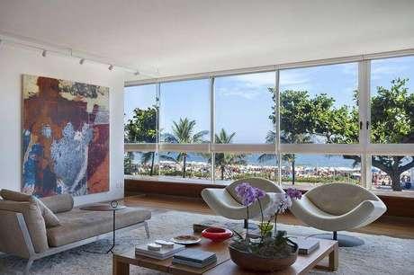 4. Janelas amplas e móveis bem dispostos, como no projeto da Escala Arquitetura ajudam a causar a sensação de um ambiente arejado na casa de praia.