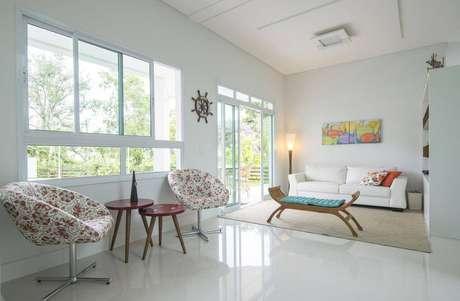 24. A sala de estar iluminada com quadro colorido é simples e bonita. Projeto por Oficio da Arte.
