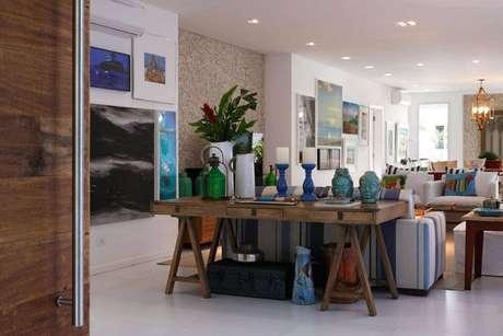 27. A sala de estar com azul e listras tem quadros na mesma cor, para harmonizar. Projeto por In House Designers.