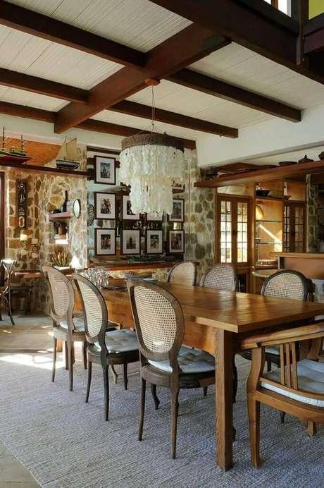 29. A sala da casa de praia completa: lustre de conchas, elementos rústicos e madeira. Projeto por Urbano Studio.