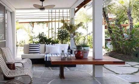 15. A varanda da casa de praia tem detalhes de listras no fundo branco. Projeto por In House Designers.