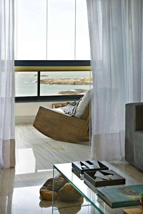 33. A varanda da casa de praia tem cadeira de balanço para apreciar a vista. Projeto por Coutinho Vilela.