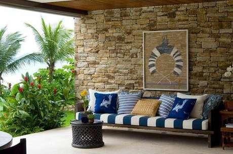 34. Vista para o verde e para o mar em um sofá com listras e várias almofadas. Projeto por Paulo Carvalho.