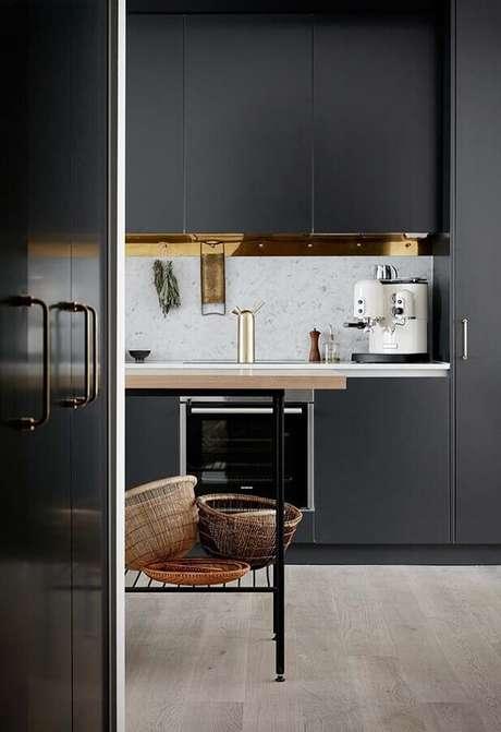 25. O detalhe dourado dá um toque sofisticado na decoração da cozinha preta planejada – Foto: Pinterest