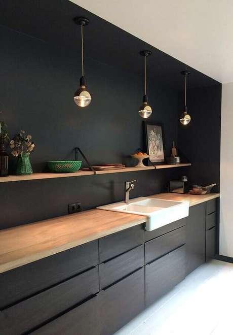28. Decoração moderna para cozinha planejada preta com bancada de madeira e pendentes redondos – Foto: Original Home
