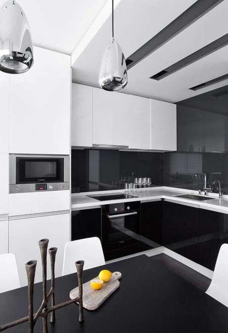 40. Cozinha preta e branca moderna planejada com pendentes prata – Foto: Ideias Decor