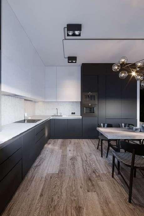 41. Decoração para cozinha preta e branca ampla com mesa e piso de madeira – Foto: Dicas Decor