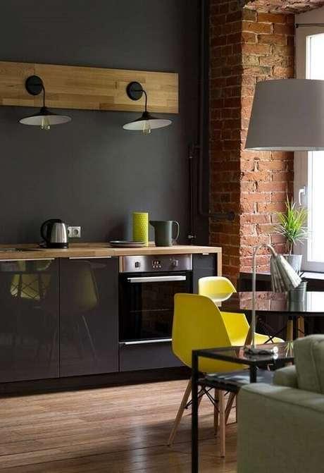 46. A parede de tijolinho à vista garante um toque rústico para a decoração da cozinha completa preta – Foto: Área Mulher