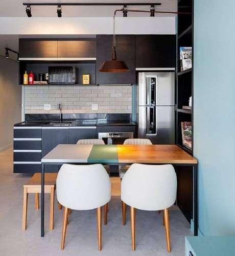 57. Decoração para cozinha compacta preta com mesa de madeira e trilho de luz – Foto: Webcomunica