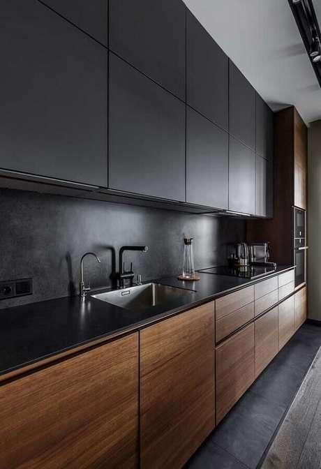 72. Cozinha planejada preta moderna decorada com armários em acabamento fosco e portas de madeira – Foto: Decoração de Casa