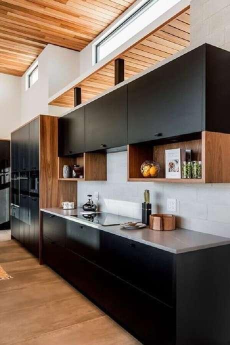 73. Nichos de madeira integrados a armário de cozinha preto – Foto: Revista VD