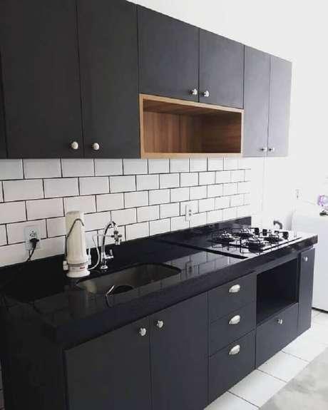 75. Decoração de cozinha preta simples com nicho de madeira – Foto: Dicas Decor
