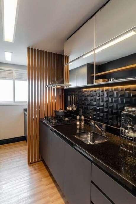 82. Revestimento 3D para decoração de cozinha compacta preta planejada com divisória de madeira para área de serviço – Foto: Revista VD