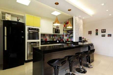 8. Decoração para cozinha americana preta com revestimento colorido e pendentes dourados – Foto: Juliana Conforto