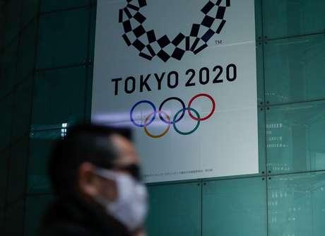 Homem com máscara de proteção passa pelo logo da Olimpíada de Tóquio 11/03/2020 REUTERS/Issei Kato
