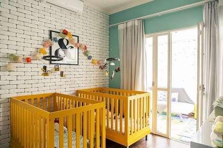 11. Berços coloridos para quarto de bebê amarelo com parede de tijolinho pintada de branca – Foto: Bebê Mamãe