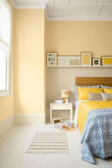 13. Decoração clean de quarto amarelo claro com cabeceira de madeira – Foto: A Casa Perfeita